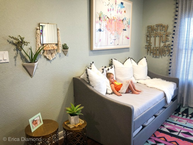 view of planters, couch, art and curtins in the playroom with a fun colorful rug