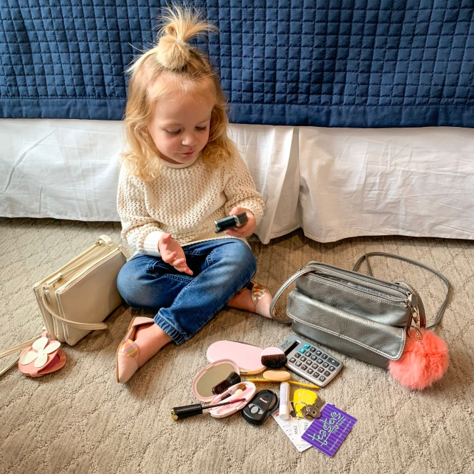 little girl play purse with household items